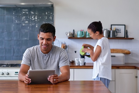 couple in kitchen, male looks at tablet