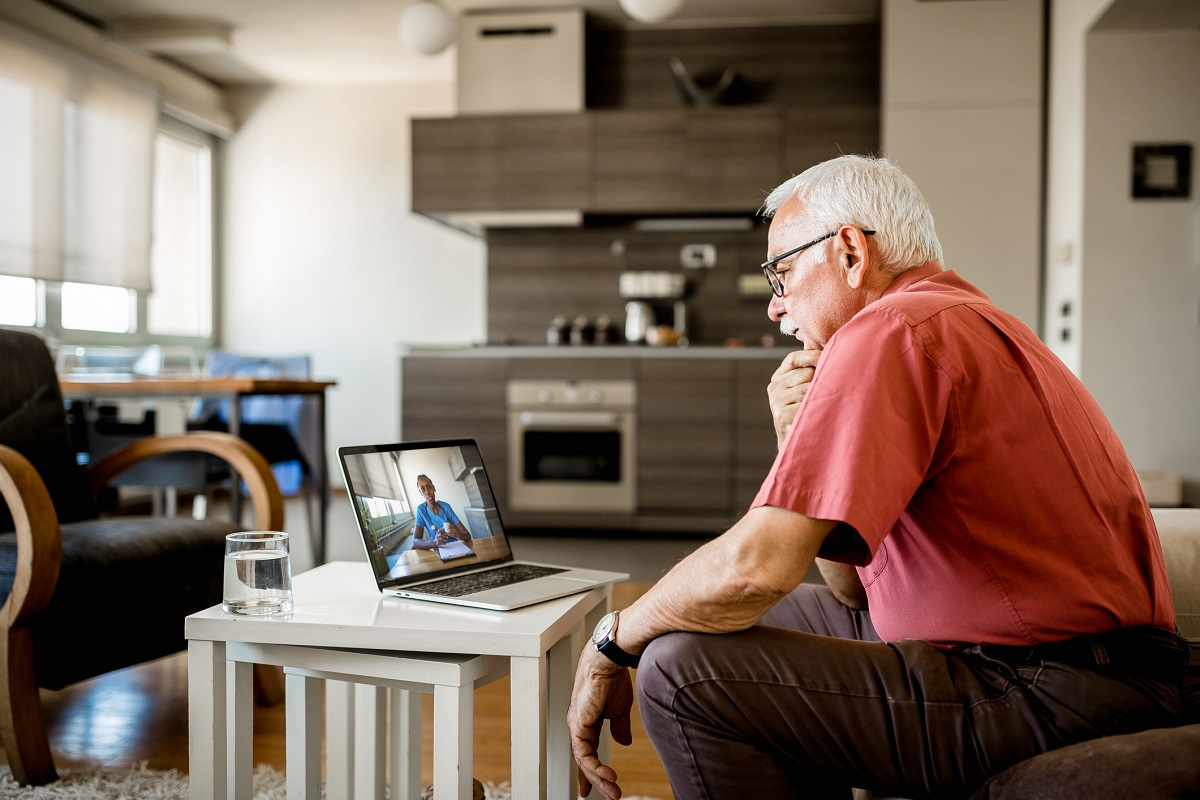 Senior White Man at home having video call with doctor